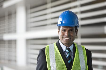 Ritratto di un maschio indiano, ingegnere industriale al lavoro. Assistente tecnico asiatico che sorride & che esamina la macchina fotografica.