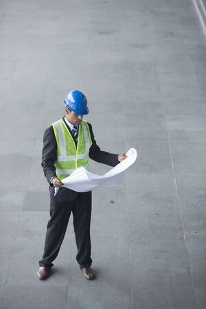 oil and gas: High angle view of an male Indian industrial engineer at work holding technical drawing plans.