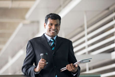 happy worker: Portrait of an Indian businessman outside modern office building.