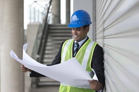 mantenimiento: Retrato de un ingeniero industrial de la India masculino en el trabajo mirando a los planes de dibujo técnico.