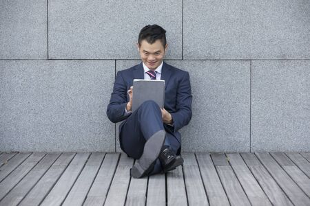 asian business man: Asian business man using digital tablet computer, leaning against a marble wall. Stock Photo