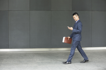 asian business man: Side view of a Chinese businessman walking outdoors and using his Smart phone in modern Asian city. Stock Photo
