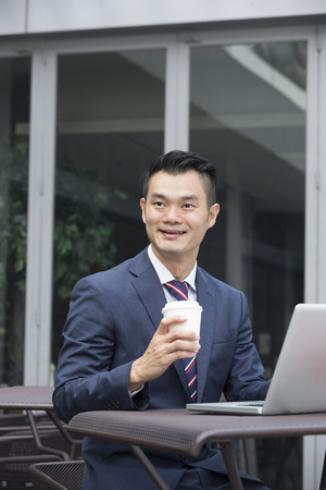 out of doors: Chinese business Man using his laptop out doors in modern city. Stock Photo