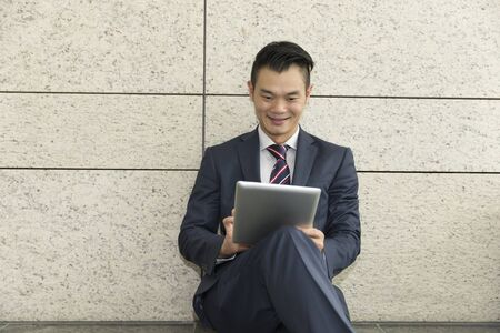 asian business man: Chinese man with a tablet computer. Asian business man using digital tablet computer, leaning against a marble wall.