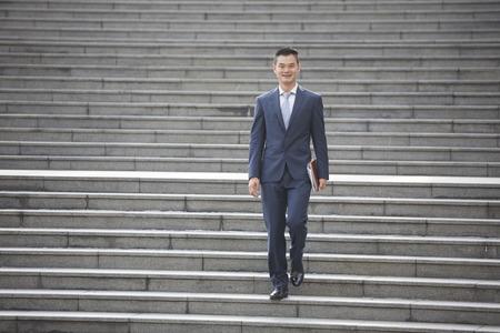 down the stairs: Retrato de un hombre de negocios feliz de Asia caminando por las escaleras. Foto de archivo
