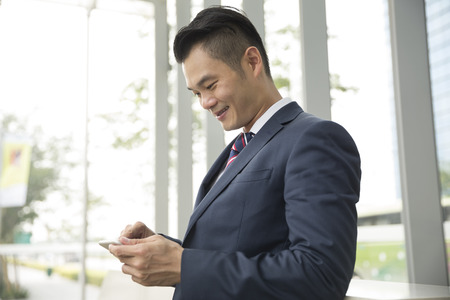 phone professional: Chinese businessman standing outdoors and using his Smart phone in modern Asian city. Stock Photo