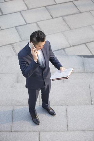 vysoký úhel pohledu: Pohled zezadu na čínského obchodníka mimo kancelář pomocí mobilního telefonu a čtení novin. Reklamní fotografie