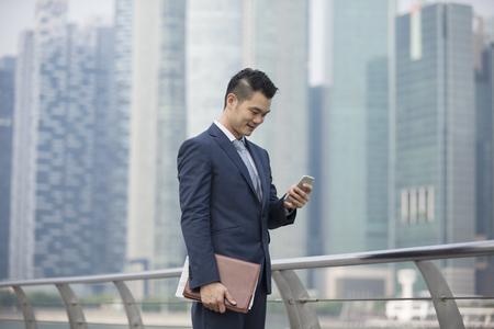 homme d'affaires chinois debout en plein air et en utilisant son téléphone intelligent dans la ville asiatique moderne.