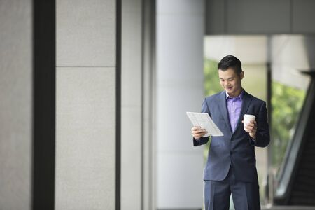 asian business man: Chinese Business man Outside Office reading a newspaper. Asian business man taking a break. Stock Photo