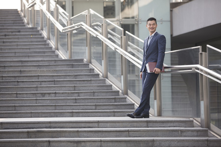 asian business man: Portrait of a happy Asian businessman standing on stairs and looking away. Chinese business man standing outdoors.