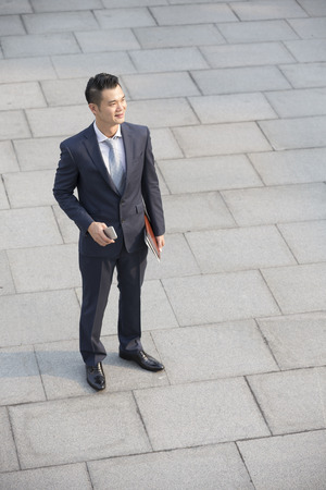pavement: High angle view of a happy Asian businessman looking away. Stock Photo