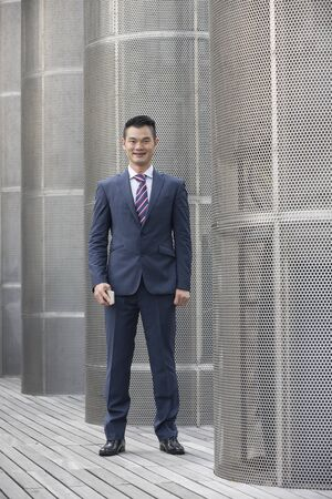 businessman in office: Chinese business man in modern Asian city. Stock Photo