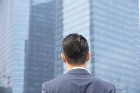 man looking: Rear view of an Asian businessman looking away. Stock Photo