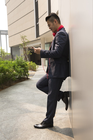 chinese businessman: Chinese businessman standing outdoors and using his Smart phone in modern Asian city. Stock Photo