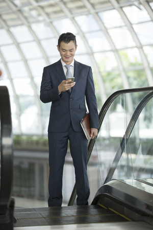 phone professional: Chinese businessman standing outdoors and using his Smart phone in modern Asian city. Business on the go concept.