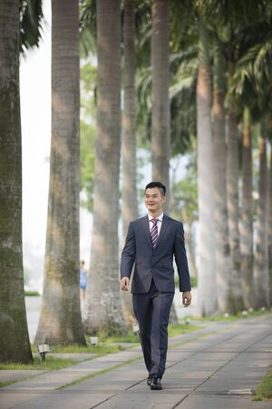 chinese businessman: Portrait of a Chinese businessman outside modern office building. Asian businessman smiling & looking at the camera.