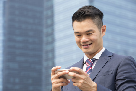 chinese businessman: Chinese businessman standing outdoors and using his Smart phone in modern Asian city. Business on the go concept.