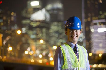 ingeniero civil: El arquitecto chino o ingeniero en el trabajo en una obra de construcción en la noche.