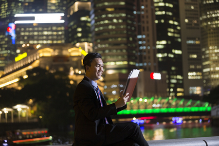 chinese businessman: Chinese businessman standing outdoors at night and looking at city skyscrapers. Stock Photo