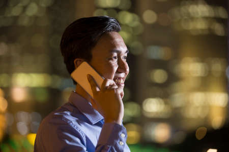 late 30s: Asian businessman outdoors talking on his Smart phone at night in modern city. Stock Photo