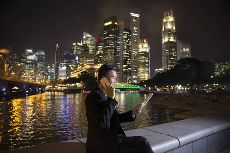 late thirties: Asian businessman outdoors talking on his Smart phone at night in modern city. Working late and Business on the go concept.