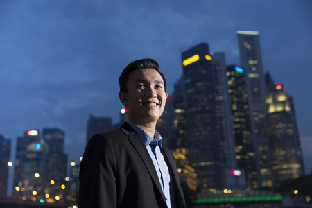 businessman in office: Chinese businessman standing outdoors at night and looking at city skyscrapers. Stock Photo
