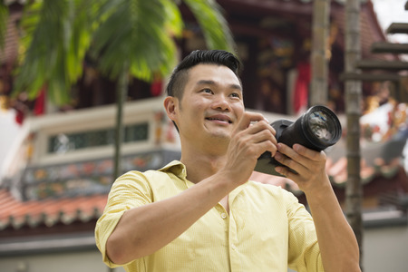 take a: Happy Asian man on holiday using his digital camera (DSLR) to take a photo.