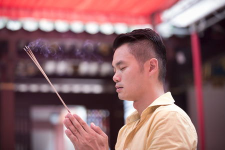 A Chinese man is praying outside a Buddhist temple and burning incense.