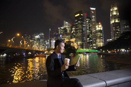 late 30s: Asian businessman outdoors using his digital Tablet PC at night in modern city.