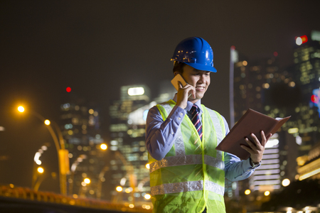 Chinese Architect or engineer at work on a building site talking on the phone at night.