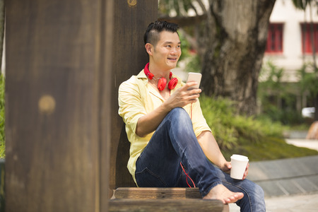 asian lifestyle: Casual Asian man relaxing outdoors and using reading his smart phone.