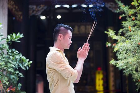 chinese courtyard: A Chinese man is praying outside a Buddhist temple and burning incense.