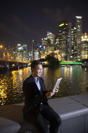 late 30s: Asian businessman outdoors using his digital Tablet PC at night in modern city. Working late and Business on the go concept. Stock Photo