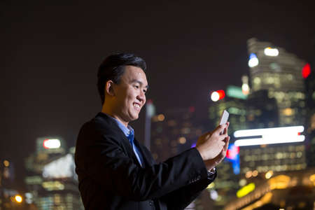 late 30s: Asian businessman outdoors using his Smart phone at night in modern city.