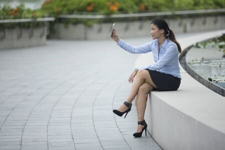 executive women: Portrait of a Chinese businesswoman making a video call on using her smart phone.