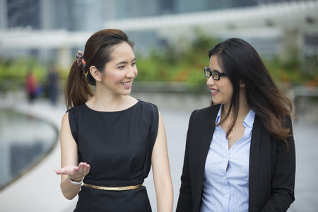Happy Chinese Business women walking outside office & talking to each other. Stock Photo