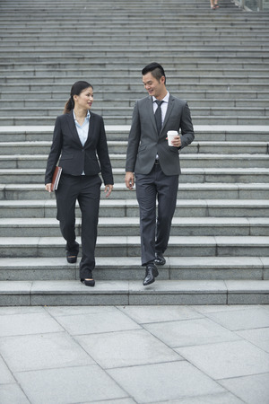 management team: Portrait of Chinese business man and woman in a modern urban setting.