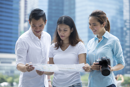 asian group: Happy Chinese tourists sightseeing with a map, camera and tablet in the city. Group of Asian friends on city break holiday. Stock Photo