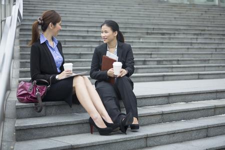 Office women: Portrait of two Asian business women talking outside modern office building. Chinese business colleague talking outside.