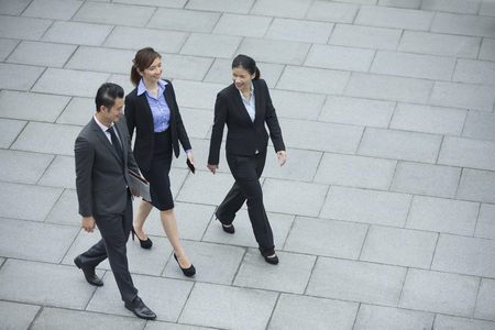 elevated view: Elevated view of three Chinese Business colleagues walking outdoors. Group of 3 Asian business men and women.