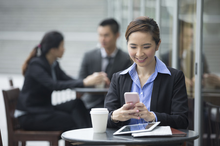 business asia: Portrait of a Chinese businesswoman using a smart phone in a cafe. Stock Photo