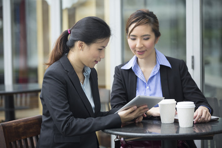 Two Chinese Business women meeting in a cafe. Female Asian business colleagues sitting in a cafe. Stock Photo