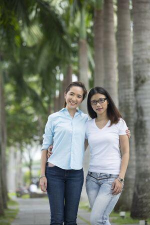 lesbians: Retrato de dos amigos de la chica asi�tico feliz en la ciudad. Foto de archivo