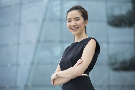 testimonial: Cheerful Chinese business woman standing outside with office buildings in the background. Portrait of an Asian business woman looking at the camera.
