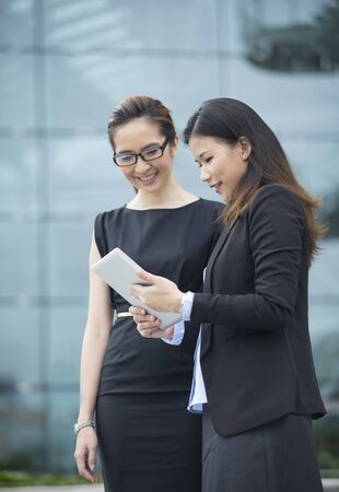 femmes souriantes: Two Chinese business women with digital tablet in a modern urban setting.