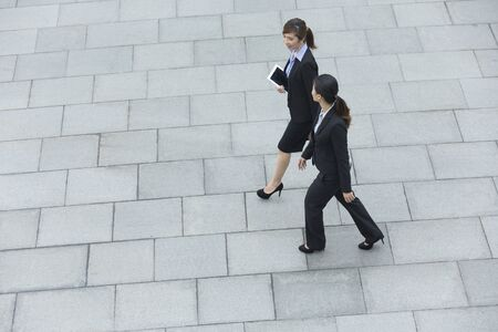 copy space: Elevated view of two Chinese business women walking outside modern office building.