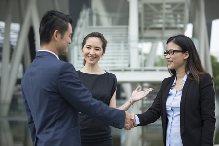 chinese businessman: Chinese Businessman and businesswoman shaking hands outside the office.