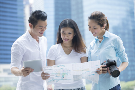 tourists: Happy Chinese tourists sightseeing with a map, camera and tablet in the city. Group of Asian friends on city break holiday. Stock Photo