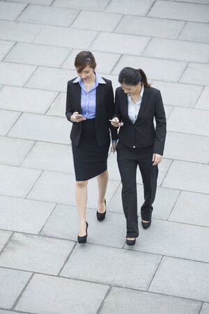 woman business suit: Two Asian Business women using there Smartphones, while walking outside. Stock Photo