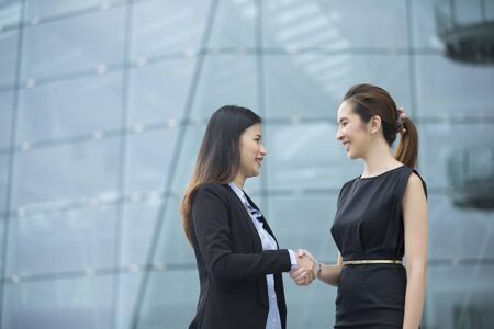 manager team: Chinese business women shaking hands outside the office. Business concept. Stock Photo
